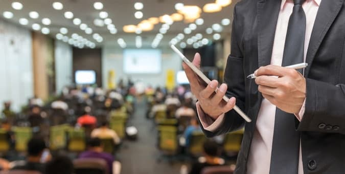 Businessman using event management software in a full conference room to improve efficiency of the event.