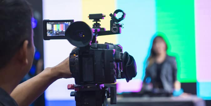 Photograph of NDI video being recorded with cameraman and news anchor