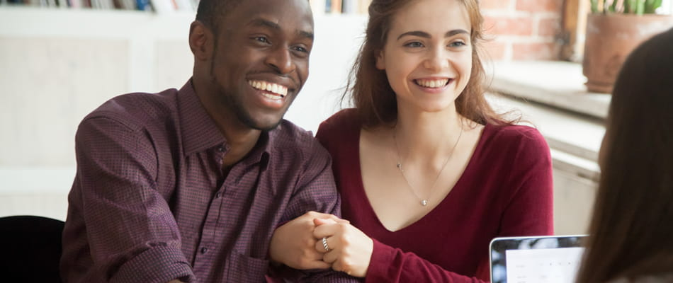 smiling multiracial couple customers shaking hands